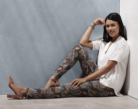 Eine Frau mit langer Jeans mit Blättermuster sitzt in einer Zimmerecke.